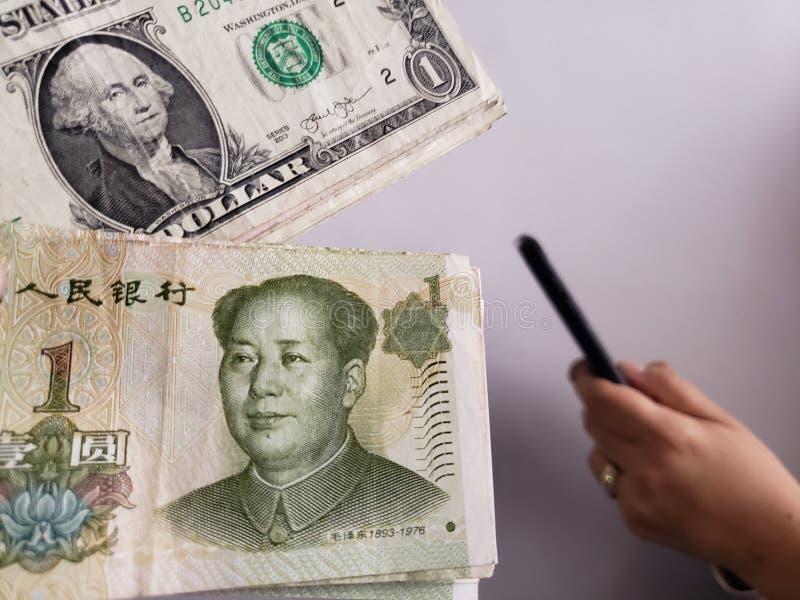 американские долларовые банкноты одно, китайские банкноты и рука держа смартфон стоковые фото