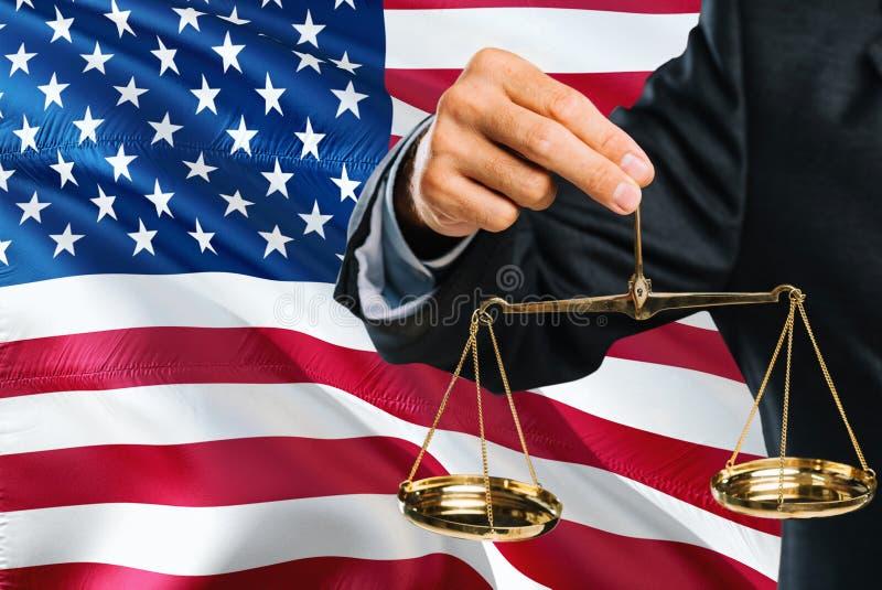 Американский судья держит золотые весы правосудия с предпосылкой флага Соединенных Штатов развевая Тема равности и законная конце стоковое фото rf