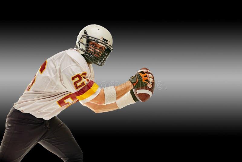 Американский футболист в движении с шариком на черной предпосылке с цепью световых маяков, космос экземпляра Концепция  стоковое изображение rf