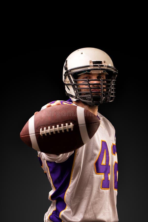 Американский футболист держа шарик в его руках перед камерой Американский футбол концепции, мотивация стоковое изображение rf