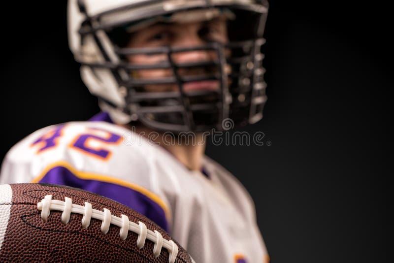 Американский футболист держа шарик в его руках перед камерой Американский футбол концепции, мотивация стоковая фотография rf
