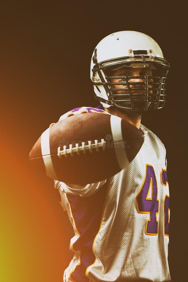 Американский футболист держа шарик в его руках перед камерой Американский футбол концепции, мотивация стоковые фотографии rf