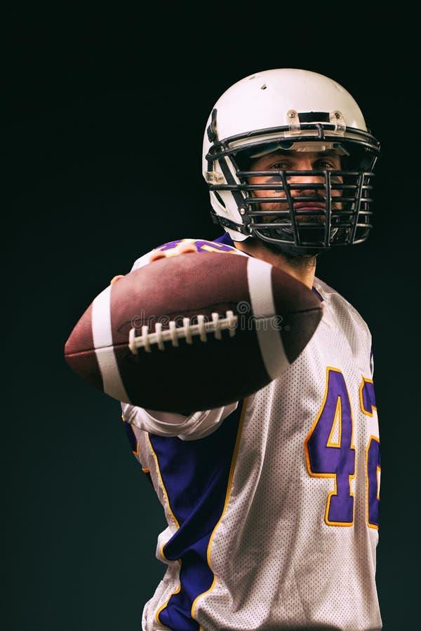 Американский футболист держа шарик в его руках перед камерой Американский футбол концепции, мотивация стоковая фотография