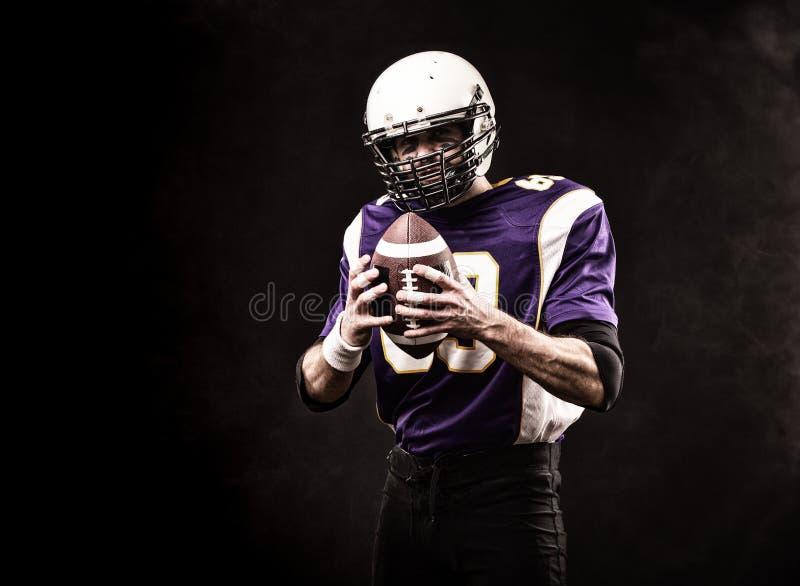 Американский футболист держа шарик в его руках Черная предпосылка, космос экземпляра Концепция американского футбола стоковое изображение rf