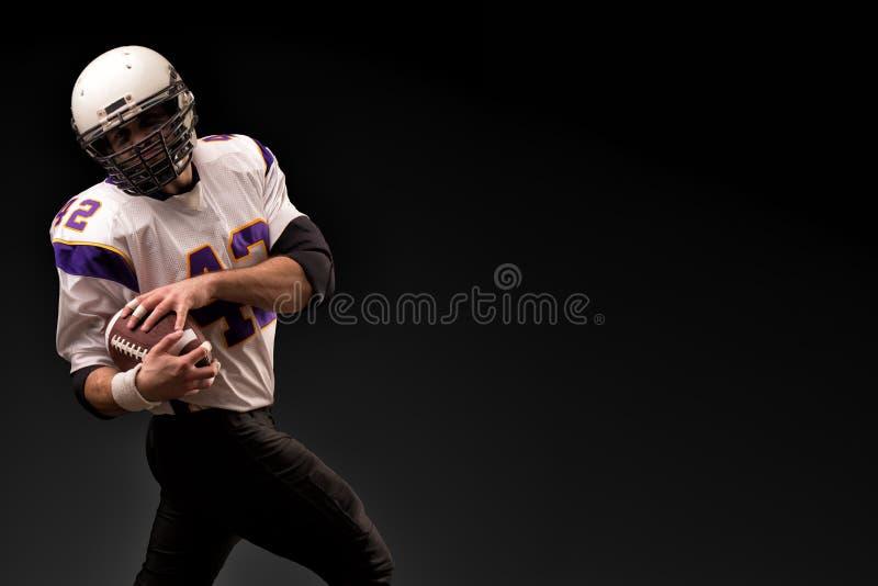 Американский футболист держа шарик в его руках Черная предпосылка, космос экземпляра Концепция американского футбола стоковое изображение