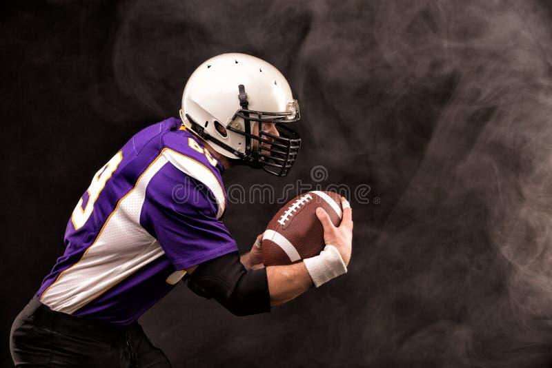 Американский футболист держа шарик в его руках Черная предпосылка, космос экземпляра Концепция американского футбола стоковые изображения