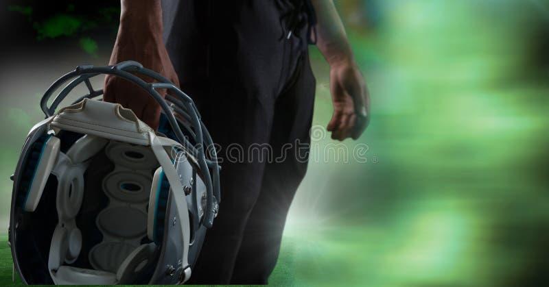 Американский футболист держа шлем с зеленым переходом стоковое фото