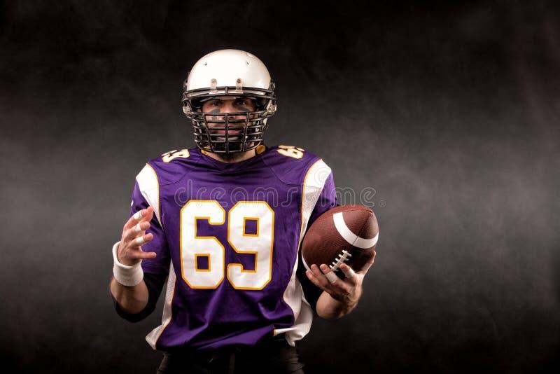Американский футболист представляя с шариком на черной предпосылке стоковое фото rf