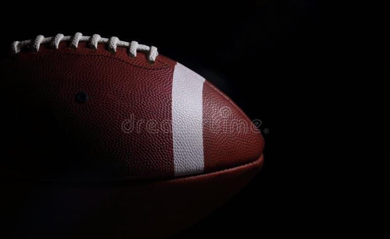 Американский футбол против черной предпосылки с Copyspace к t стоковые изображения