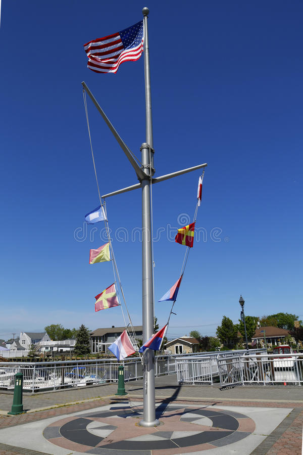 Американский флаг и морские флаги летая на эспланаду в Фрипорте, Лонг-Айленд Woodcleft стоковые фото
