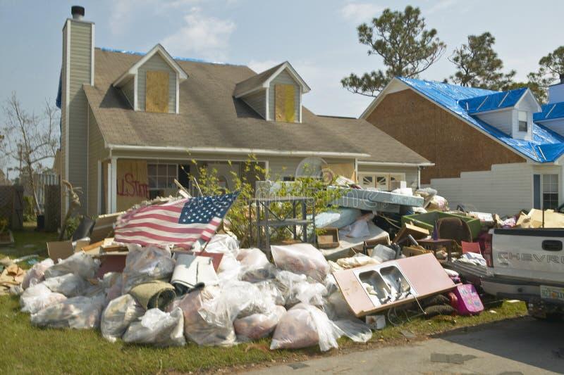 Американский флаг и твердые частицы перед домом тяжело ударили ураганом Иваном в Pensacola Флориде стоковое изображение rf