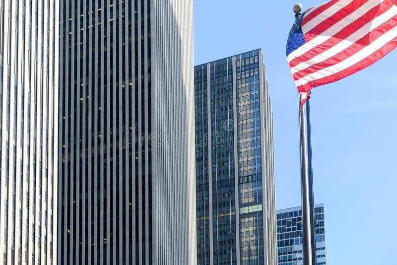 Американский флаг развевая небоскребами Нью-Йорка стоковая фотография