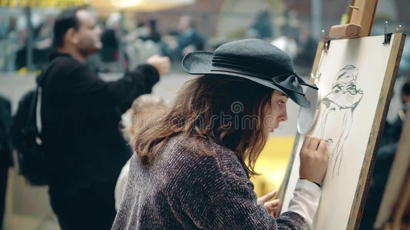 АМСТЕРДАМ, НИДЕРЛАНДЫ - 26-ОЕ ДЕКАБРЯ 2017 Красивая молодая женщина рисуя автопортрет Состязание искусства дилетанта стоковые фото