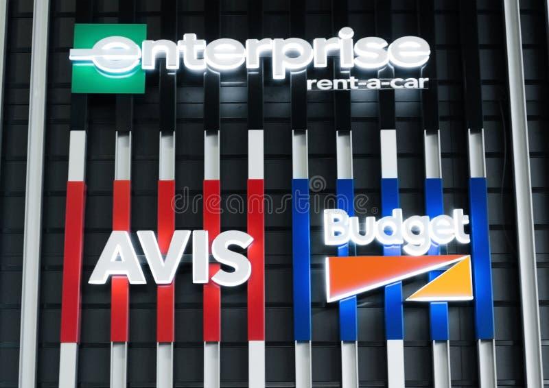 АМСТЕРДАМ, НИДЕРЛАНДЫ - 18-ОЕ ИЮЛЯ 2018: Афиша прокатного автомобиля бюджета Avis Enterprice на стали обнести авиапорт стоковые фотографии rf