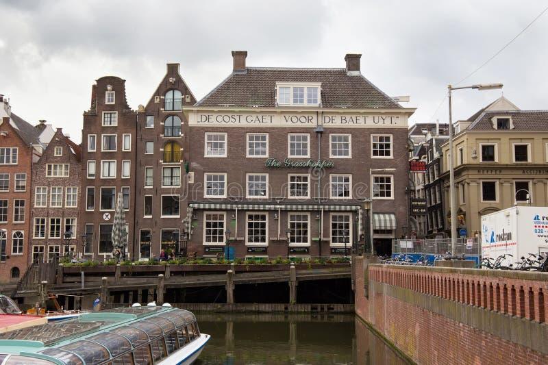 АМСТЕРДАМ, НИДЕРЛАНДЫ - 25-ОЕ ИЮНЯ 2017: Взгляд к старым историческим голландским зданиям от улицы Damrak стоковые изображения
