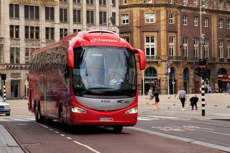 АМСТЕРДАМ, НИДЕРЛАНДЫ - 25-ОЕ ИЮНЯ 2017: Красный туристический автобус Irizar на квадрате запруды в историческом центре Амстердам стоковая фотография