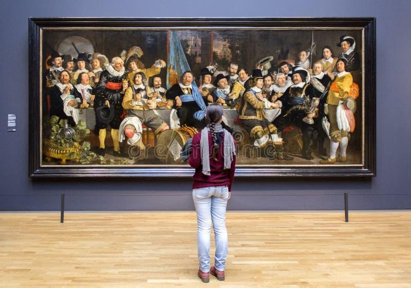 АМСТЕРДАМ, НИДЕРЛАНДЫ - 8-ОЕ ФЕВРАЛЯ: Посетитель на Rijksmuseum дальше стоковая фотография