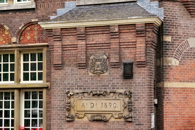 АМСТЕРДАМ, НИДЕРЛАНД - 25-ОЕ ИЮНЯ 2017: Разделите старую стену здания красных кирпичей на улице Oudezijds Voorburgwal стоковое изображение