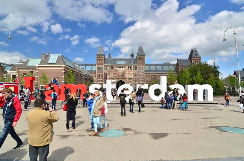 Амстердам, Нидерланды - 6-ое мая 2015: Туристы на известном знаке стоковые фотографии rf