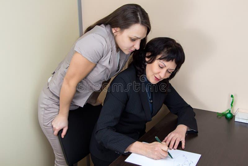 2 дамы дела в думать офиса стоковое фото rf