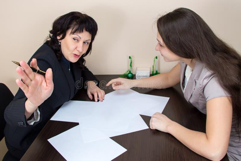 2 дамы дела сидя в офисе и говорить стоковое изображение rf
