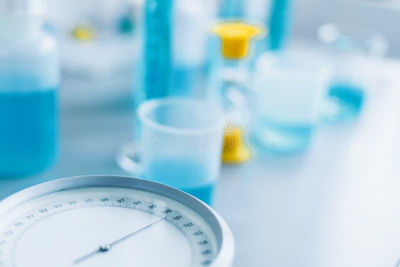 Анализ качества жидкостей в химической лаборатории, приборе с оборудованием изготовленным стекла с голубой жидкостью стоковое изображение