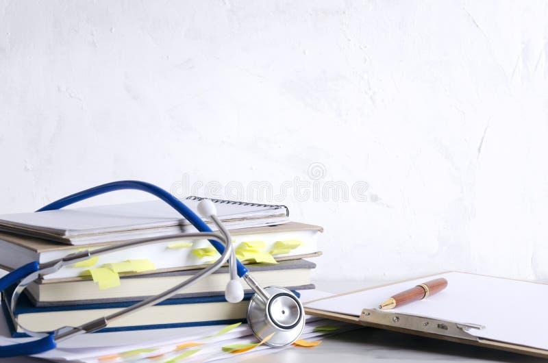Анамнез, стетоскоп, доска сзажимом для бумаги с чистым листом бумаги, ручкой на таблице против белой стены Концепция приема и pre стоковое изображение