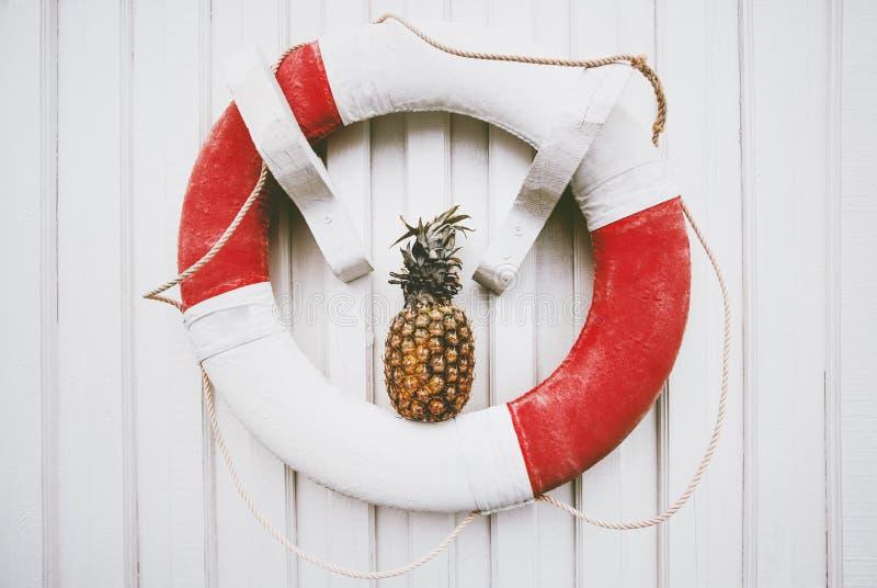 Ананас каникул перемещения лета и lifebuoy на белой деревянной стене стоковые фото