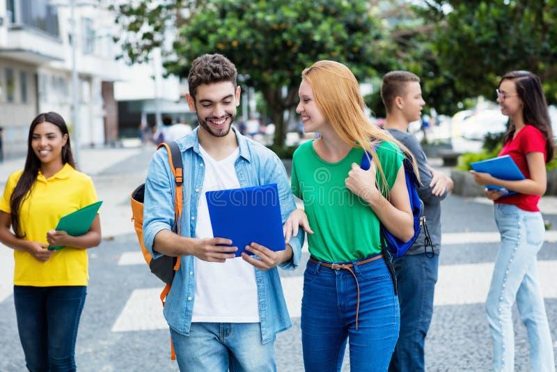 Английская студентка и испанский парень с группой в составе mutliethnic студенты стоковые фотографии rf