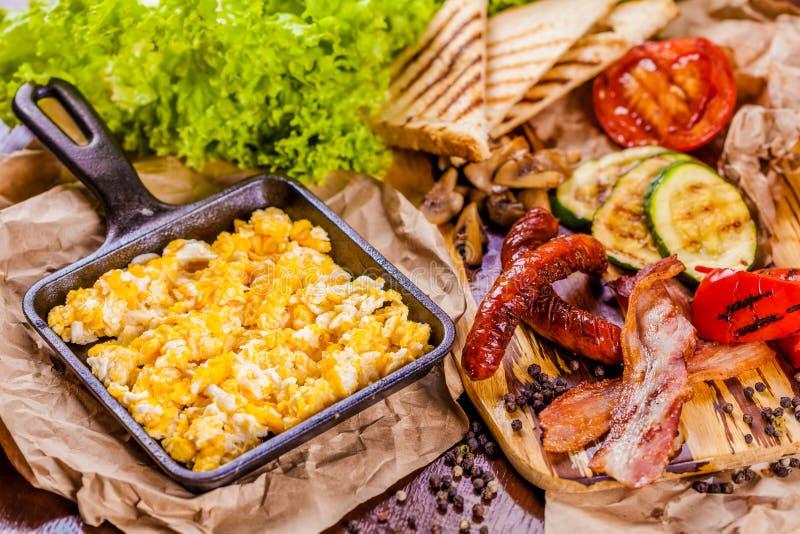 Английский завтрак с взбитыми яйцами, сосисками, беконом, овощами стоковые фотографии rf