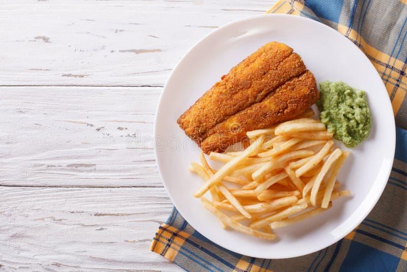 Английская еда: зажаренные рыбы в бэттере с обломоками по горизонтали верхняя часть VI стоковые фото