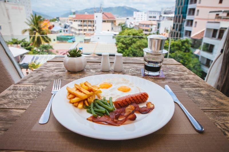 Английский завтрак с яичницами, беконом, сосисками, зелеными фасолями и фраями француза стоковые изображения rf