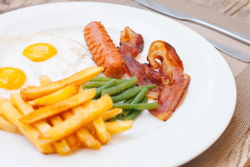 Английский завтрак с яичницами, беконом, сосисками, зелеными фасолями и фраями француза стоковое фото rf