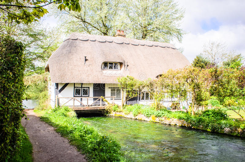 Английский покрыванный соломой коттедж над пропуская рекой стоковая фотография