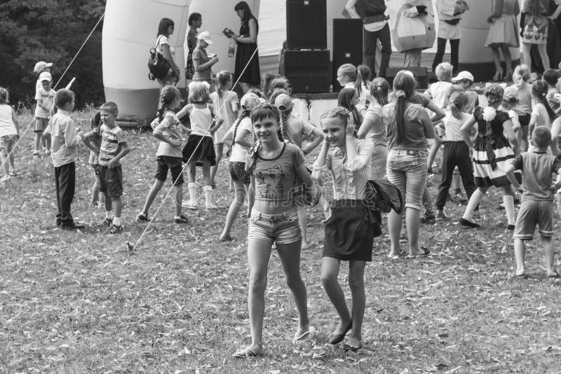 Аниматоры на этапе развлекают детей на дне фестиваля деревни Kamennomostsky в phot парка осени черно-белом стоковые фото