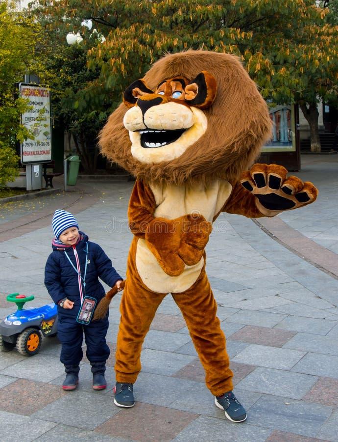 Аниматор в детях костюма льва занимательных в городе обваловки Ялты стоковая фотография rf