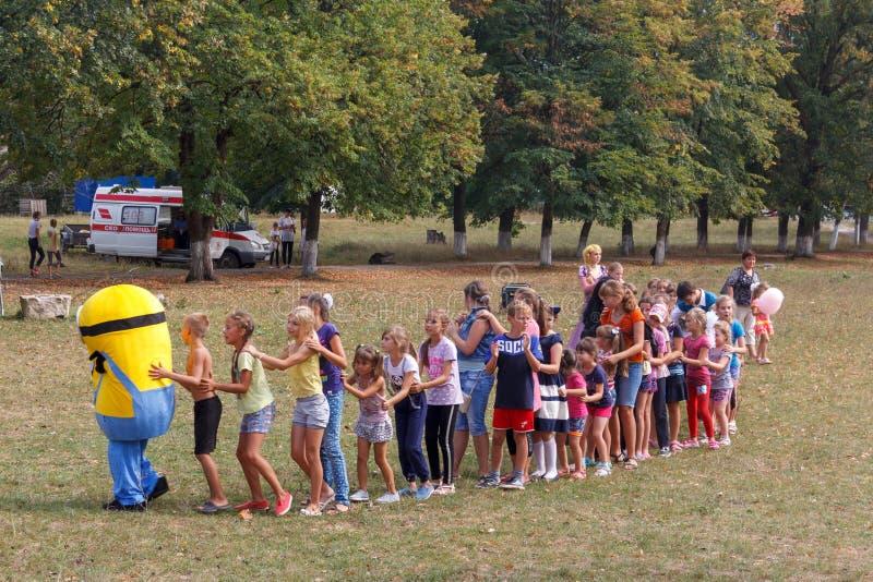 Аниматор в костюме миньона играя с детьми на праздник деревни Kamennomostskiy в равенстве осени стоковая фотография rf