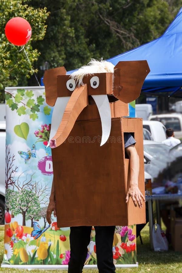 Аниматор в стилизованном костюме слона двигает на лужайку парка города стоковые фото
