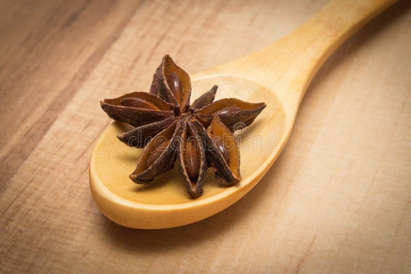 Анисовка звезды с деревянной ложкой на деревянной доске, приправляя для варить или печь стоковые фотографии rf