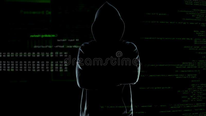 Анонимный хакер в hoodie с оружиями пересеченными на предпосылку номеров и кодов стоковые изображения