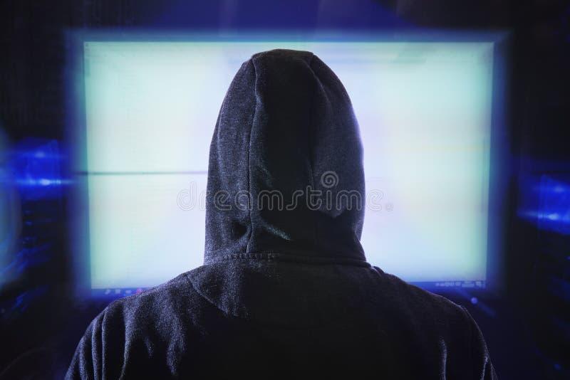 Анонимный хакер смотрит на монитор компьютера Просмотреть сзади стоковое изображение