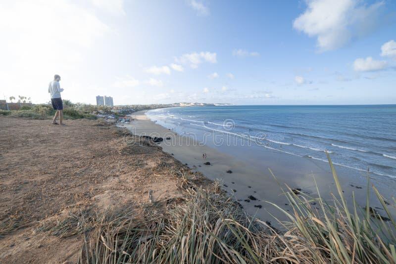 Анонимный человек идя к краю скалы, где можно увидеть пляж и море стоковые изображения