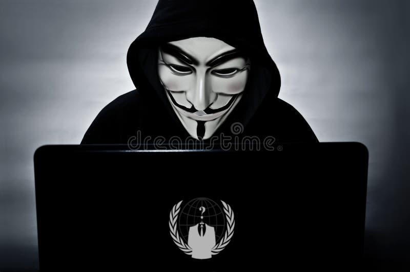 Анонимный член с компьютером с маской вендетты стоковые фото