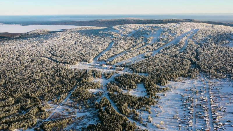 Антенна лыжного курорта с фуникулярным в снежном лесе в солнечном дне footage Ландшафт зимы снежной горы стоковые изображения rf