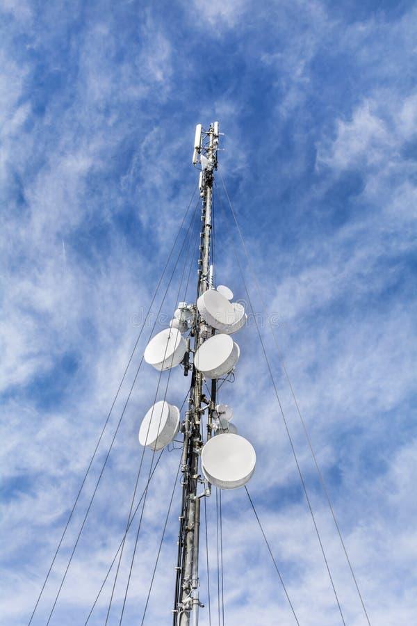 Антенны на передвижной сети возвышаются на голубом небе Глобальная система для мобильных телефонных связей стоковая фотография