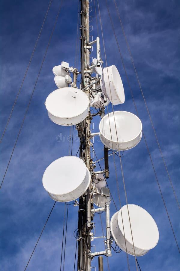 Антенны на передвижной сети возвышаются на голубом небе Глобальная система для мобильных телефонных связей стоковые фотографии rf