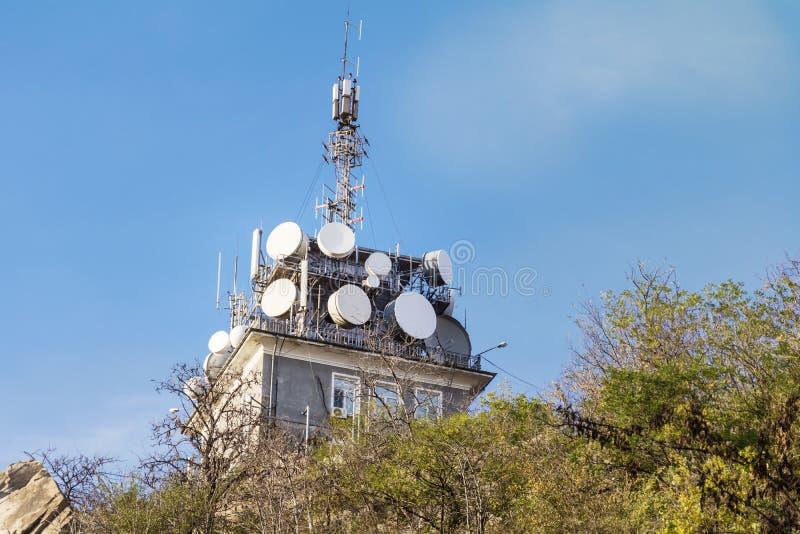 Антенны на передвижной сети возвышаются на голубом небе Глобальная система для мобильных телефонных связей стоковая фотография rf