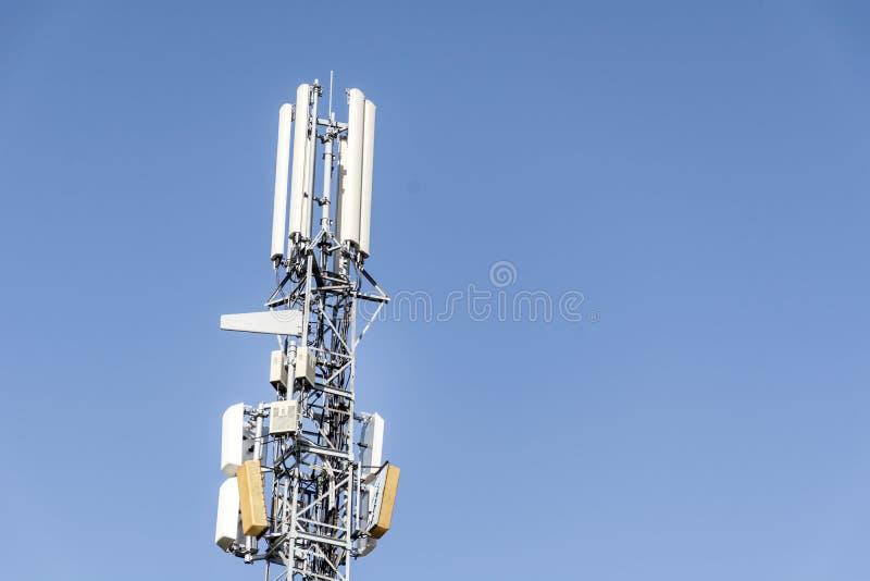Антенны на передвижной сети возвышаются на голубом небе Глобальная система для мобильных телефонных связей стоковое фото rf
