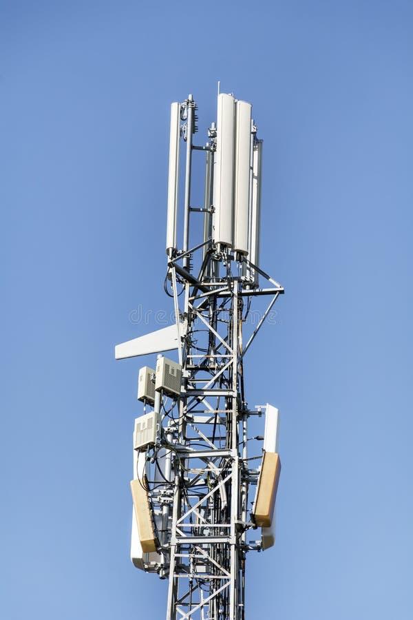 Антенны на передвижной сети возвышаются на голубом небе Глобальная система для мобильных телефонных связей стоковые фото