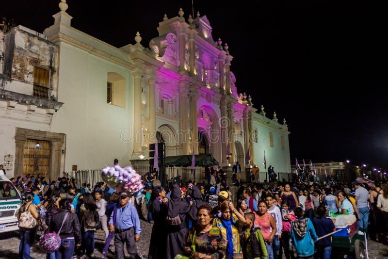 АНТИГУА, ГВАТЕМАЛА - 25-ОЕ МАРТА 2016: Участники шествия на страстной пятнице пройти собор Сантьяго внутри стоковые фотографии rf